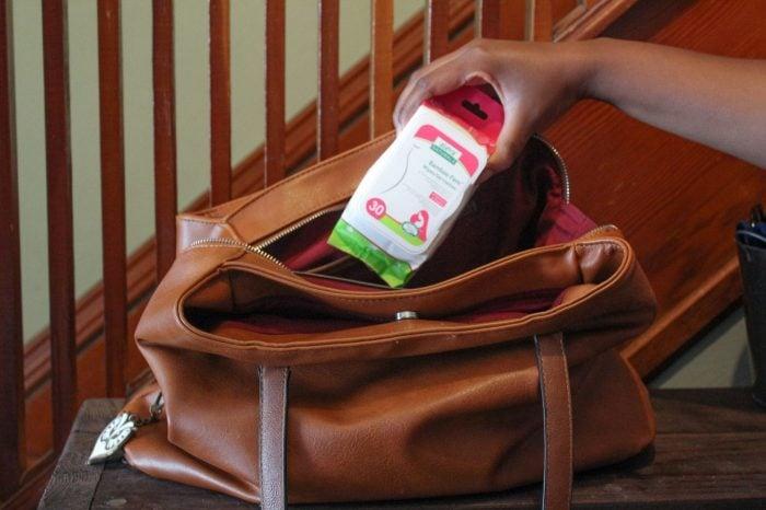 Hand placing Bambino's Fem Wipes into a purse.