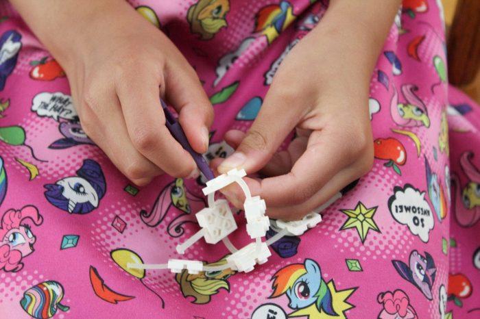 Girl's hands building Flexo GID Bracelet Set