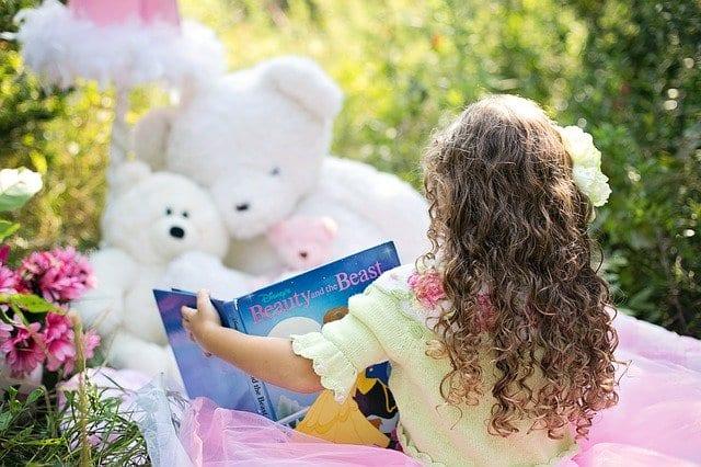 Girl reading to her plush toys