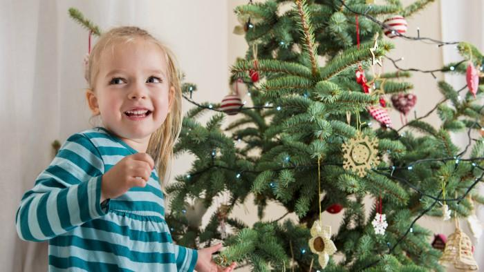 Girl decorating a real Christmas tree