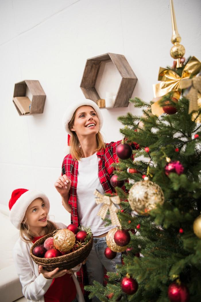woman and girl decorating a Christmas Tree