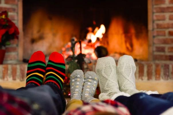family sitting in front of the fireplace showing their socks