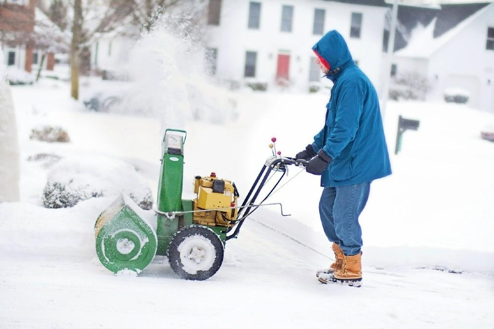 man plowing snow with a snow blower