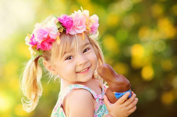 girl holding a chocolate bunny on Easter