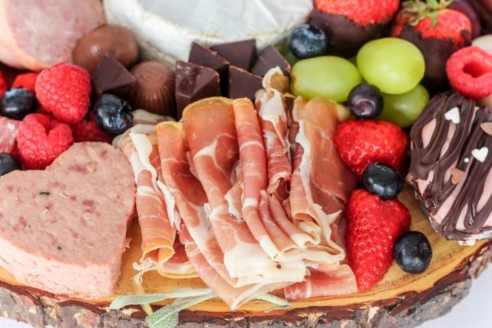 charcuterie board with meats, fruits, cheese and sweets