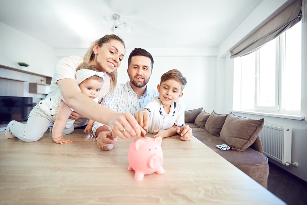 Family putting saving money in a piggy bank