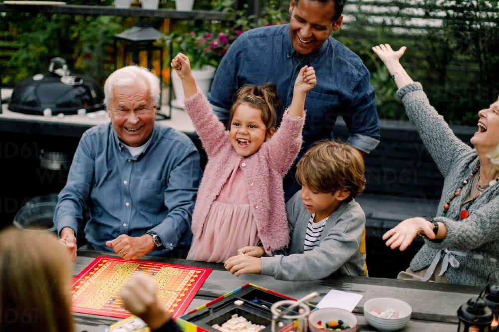 Cheerful multi-generation family playing board game on table while sitting in patio