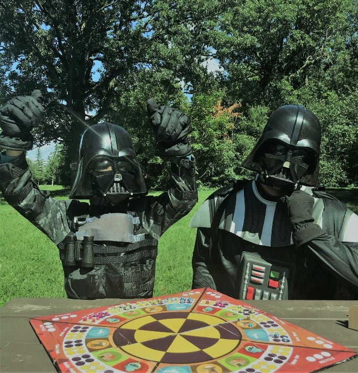 parent and child dressed as Darth Vader playing PowerFam