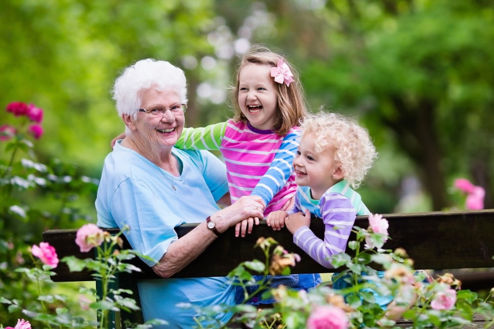 Happy senior lady playing with little boy and girl in blooming rose garden.
