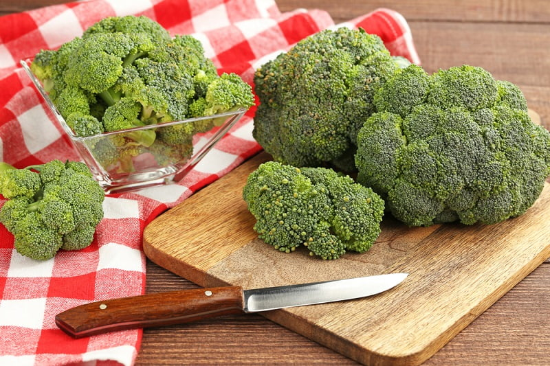Fresh broccoli on brown cutting board with knife and red napkin