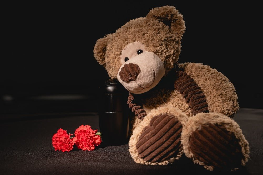 Teddy Bear beside urn with ashes