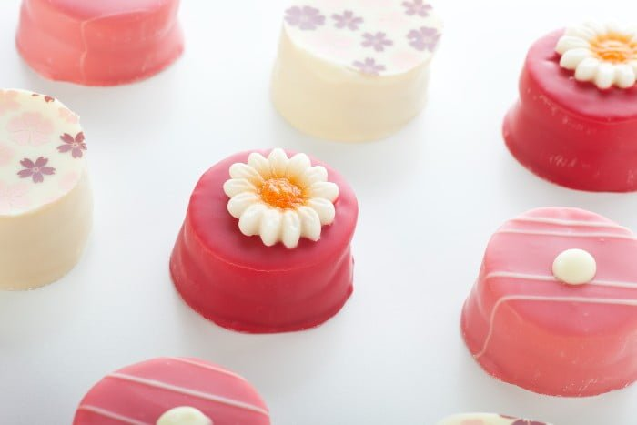 Several pink petits fours with various decorations.